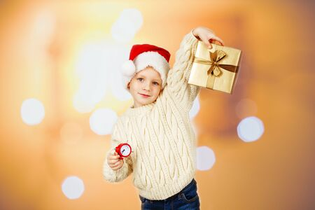 A little boy in a santa hat and in a warm knitted sweater holds a gift in a box and a small red alarm clock in front of Bokeh lights background. We celebrate the New Year and Christmas.