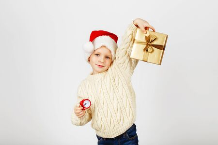 A little boy in a santa hat and in a warm knitted sweater holds a gift in a box and a small red alarm clock. We celebrate the New Year and Christmas. Stock Photo