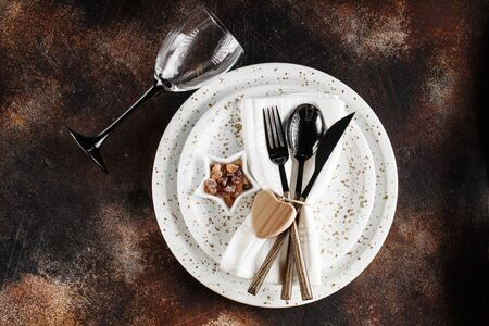 Festive table place setting. Crockery and cutlery on a dark textured background with copy space. Christmas Xmas New Year holiday background 스톡 콘텐츠