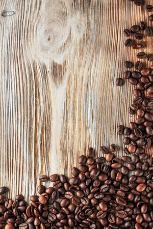 Black coffee beans studio shot. Freshly roasted coffee beans on the wooden texture background