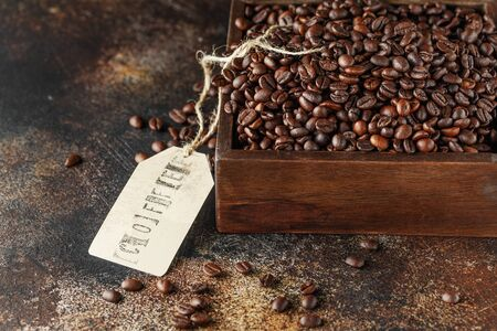 Black coffee beans studio shot. Freshly roasted coffee beans in a wooden box