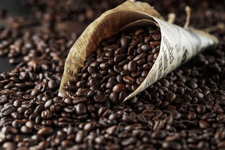 Black coffee beans studio shot. Freshly roasted coffee beans in a cone of paper