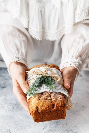 Stollen is a fruit bread of nuts, spices, and dried or candied fruit, coated with powdered sugar. It is a traditional German bread eaten during the Christmas season. stollen in female hands