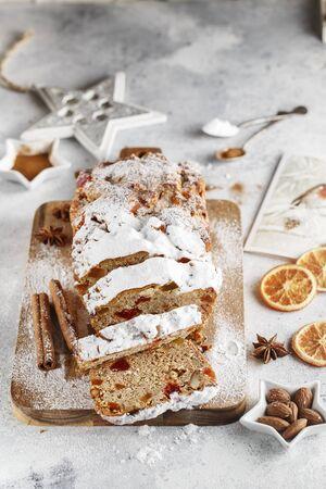 Stollen ist ein Fruchtbrot aus Nüssen, Gewürzen, getrockneten oder kandierten Früchten, umhüllt mit Puderzucker. Es ist traditionelles deutsches Brot, das während der Weihnachtszeit gegessen wird. Neujahrsvorbereitung. Festtagsbacken Standard-Bild