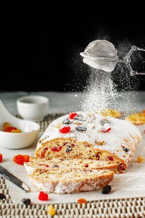 Urlaub backen. Mit Puderzucker überzogener Weihnachtskuchen. Schließen Sie die Hände des Küchenchefs mit Metallsieb, das Kuchen mit Puderzucker in der Konditoreiküche besprüht. Konditor streut Zuckerpulver Süßwaren Standard-Bild