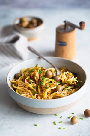 Spaghetti with Fresh Tomato Sauce, green olives and chives. Italian cuisine. Food photography, food styling.