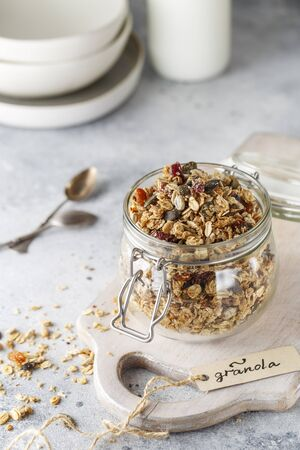 Organic homemade granola cereal with oats, nuts and dried berries. Muesli in a glass jar. Healthy vegan breakfast or snack. Copy space for text. Proper nutrition concept. Breakfast cereal.