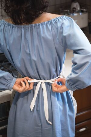 Woman puts on an apron, view from the back. Brunette girl ties an apron straps. The housekeeper in the kitchen knots an apron while preparing to prepare food for the whole family. Domestic life. Stock Photo