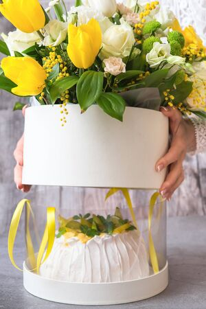 Gift set - Pavlova cake with cream and fresh fruits - lime, carambola and green mint leaves and a large Spring medley bouquet of beautiful flowers. Valentines Day. Happy Mothers day. Hands in the shot Zdjęcie Seryjne