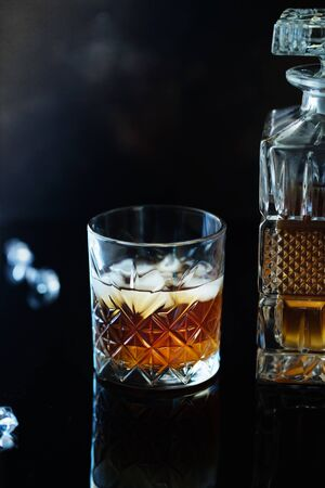 Glass of whiskey or bourbon with ice on black stone table. Glass of whiskey with ice and a square decanter. Glass of scotch whiskey and ice.