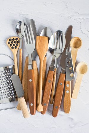 Vintage cutlery on a white background. Silver spoons, forks, table knives with wooden handles, grater. Imagens