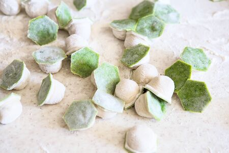 raw two-tone white and green dumplings with spinach, cheese or meat on a table with flour Stock Photo