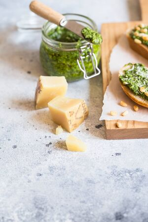 Toasts with traditional Italian basil pesto sauce on a light grey stone table. Green pesto with pine nuts and parmesan.