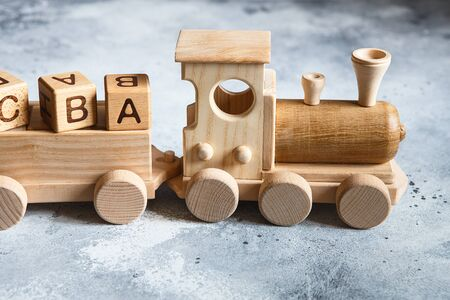 Children's wooden toys. Children wooden train with wagons. Natural wood construction set. Educational equipment. Children's wooden locomotive with various cargo in wagons. Stock Photo - 149753299