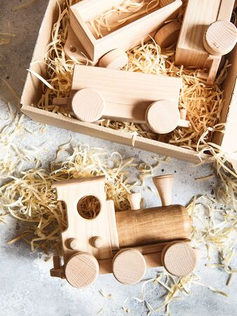 Children's wooden toys. Children wooden train with wagons in the box with sawdust. Natural wood construction set. Educational equipment.