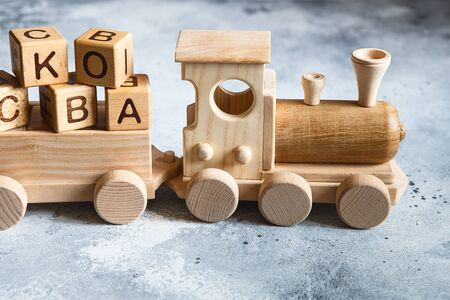 Children's wooden toys. Children wooden  train with wagons. Natural wood construction set. Educational equipment Stock Photo