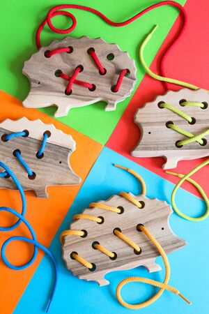 Natural wooden lacing toy hedgehog for educating fine motor skills, hand eye coordination, mathematical skills. Montessori materials. Development, education. Preschool children educational toys. Stock Photo - 149900289