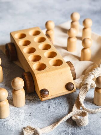 Children's wooden toys. Children wooden car with passengers. Natural wood construction set. Educational equipment. Stock Photo
