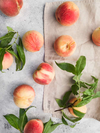 Several ripe juicy peaches on a gray background. Peach fruits on the wooden board. Green living concept. Organic food. Stock Photo