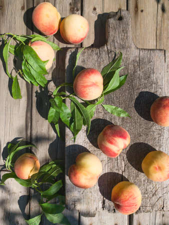 Several ripe juicy peaches on a wooden surface. Peach fruits on the wooden board. Green living concept. Organic food.
