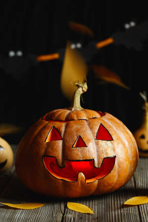 Halloween design with pumpkins. Horrible symbol of Halloween - Jack-o-lantern. Scary head of pumpkin with flame and a few small painted gourds. Glowing face, trick or treat. Halloween DIY Фото со стока