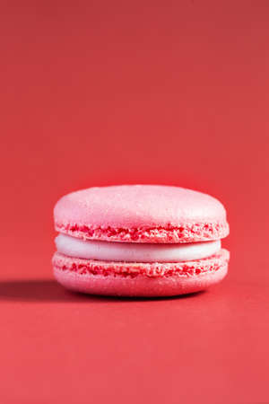 pink Cake macaron or macaroon on red background. colorful almond cookies. French macaroon cake close-up. Macaroons on colored background