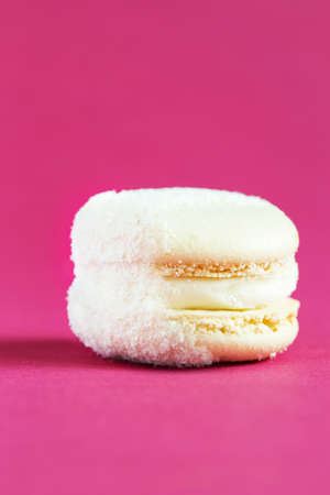 white Cake macaron or macaroon on pink background. colorful almond cookies. French macaroon cake close-up. Macaroons on colored background