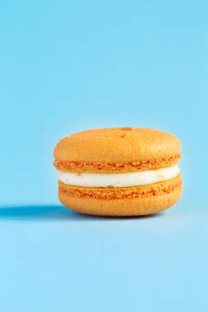orange Cake macaron or macaroon on blue background. colorful almond cookies. French macaroon cake close-up. Macaroons on colored background