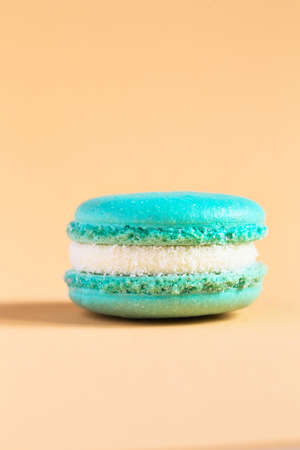 turquoise Cake macaron or macaroon on yellow background. colorful almond cookies. French macaroon cake close-up. Macaroons on colored background