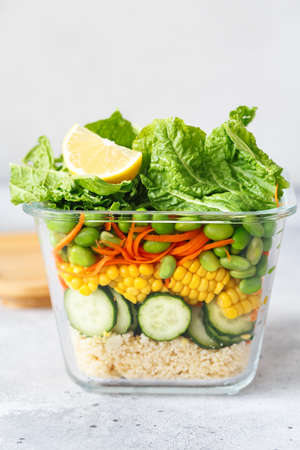 Glass box with fresh raw vegetable salad. Healthy Meal recipe preparation. Healthy vegan dish in glass container. Vegetarian cuisine. Plant-based dishes. Green living concept. Organic natural foods.