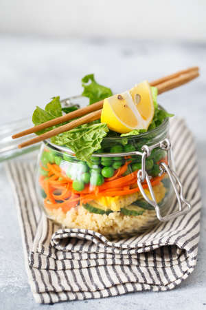 Glass jar with fresh raw vegetables and couscous groats. Healthy Meal Prep - recipe preparation photos. Healthy vegan dishes in glass containers. Weight loss food concept. Salad in a jar with chopsticks.