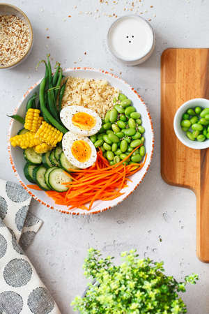 Healthy salad with couscous, carrots, cucumber, green beans, soybeans, corn and an egg on a gray concrete background. Food and health. Buddha bowl salad. Organic natural foods. Plant-based dishes.