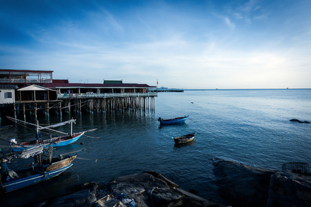 guesthouse: Fishing boat and guesthouse  at sunrise Stock Photo