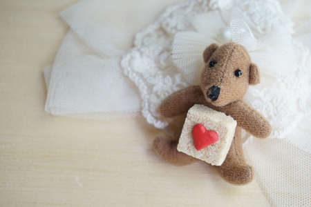 sweet heart: Little bear with sugar cube decorated by little red heart on pastel lace and wood, Sweet theme for love season. Stock Photo