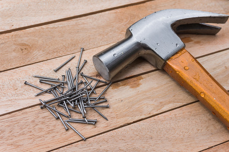 construction nails: Hammer and nails on wood background