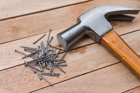 martillo: Martillo y clavos sobre fondo de madera