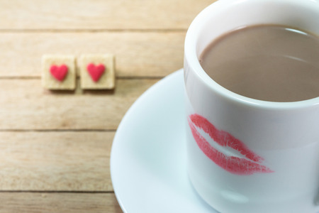 hot lips: Ceramic coffee cup with lipstick mark on wood background