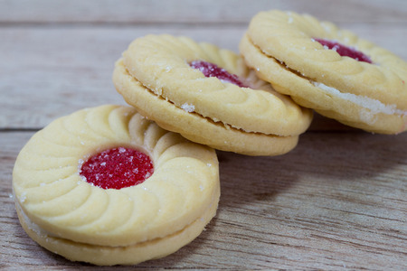 strawberry jam sandwich: Sweet cookies with cream and jam on wood background