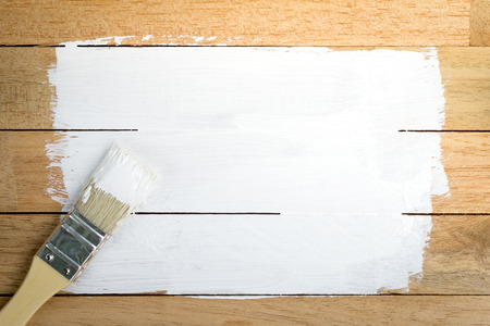 splatter: White paint space with paintbrush on wood background Stock Photo