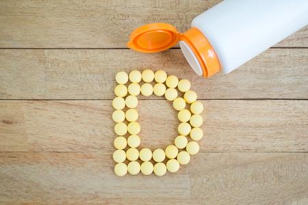 Gele pillen die vorm D alfabet op houten achtergrond Stockfoto - 53649602
