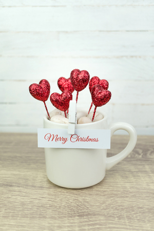Greeting message on white paper clipped on  coffee cup with glitter red heart