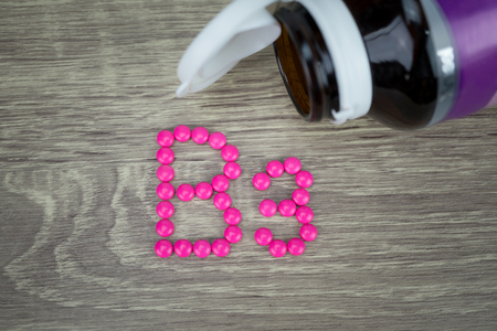 nicotinic: Pink pills forming shape to B3 alphabet on wood background
