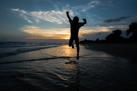 fling: Silhouette of child jumping on the beach  Stock Photo