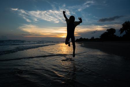 saltar: Silueta de niño saltando en la playa