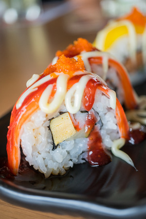 Crab stick sushi roll with strawberry sauce,  japanese food style on black ceramic dish