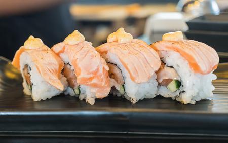 Grilled salmon sushi roll,  japanese food style on black ceramic dish  Stock Photo