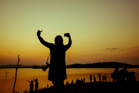 The silhouette of a woman raise her hands up among the crowd near the water in the sunset