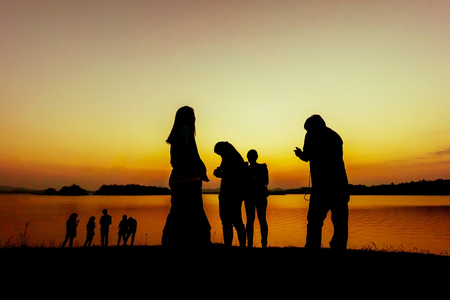 The silhouette of group of peoples near the water during sunset time