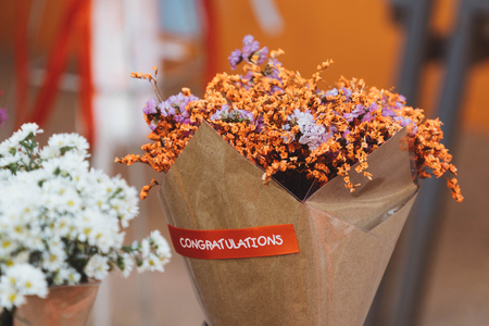 Bouquet of dried orange flowers wrapped in paper with congratulation label
