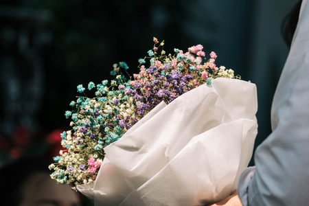 Hand holding bouquet of dried gypsophila flowers wrapped in paper Stok Fotoğraf